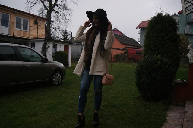 Czarny kapelusz, spodnie z dziurami i botki